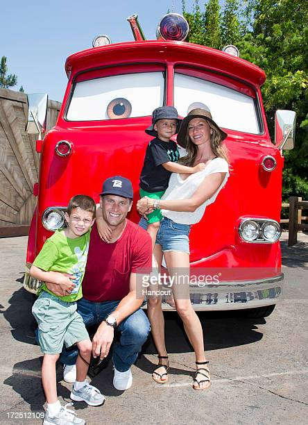 In this handout photo provided by Disney Parks Tom Brady his son Jack Gisele Bundchen and their son Benjamin pose with Red the Fire Truck at Cars...