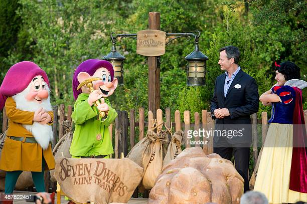 In this handout photo provided by Disney Parks Tom Staggs chairman of Walt Disney Parks Resorts joins Disney characters Sleepy Dwarf Dopey and Snow...