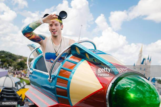In this handout photo provided by Disney Parks Twenty One Pilots drummer Josh Dun takes flight aboard the Astro Orbiter on February 27 2017 at Magic...