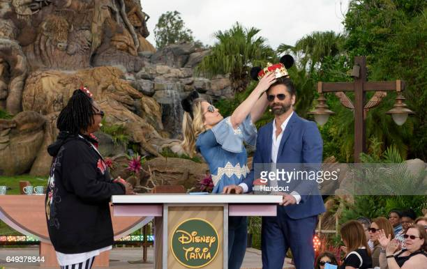 In this handout photo provided by Disney Resorts 'The View' hosts Whoopi Goldberg and Sara Haines give guest John Stamos fancy Mickey Mouse ears on...