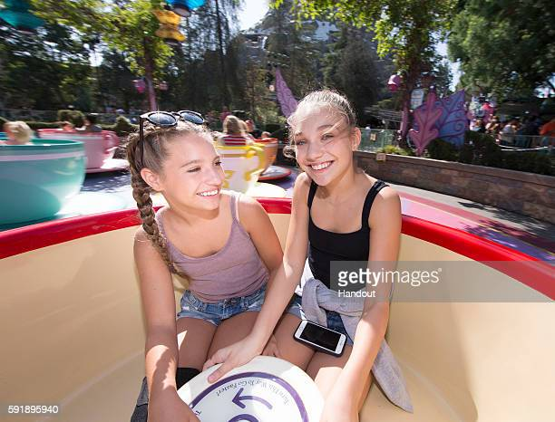 In this handout photo provided by Disneyland Resort sisters Mackenzie Ziegler and Maddie Ziegler take a spin in a teacup at the Mad Tea Party at...