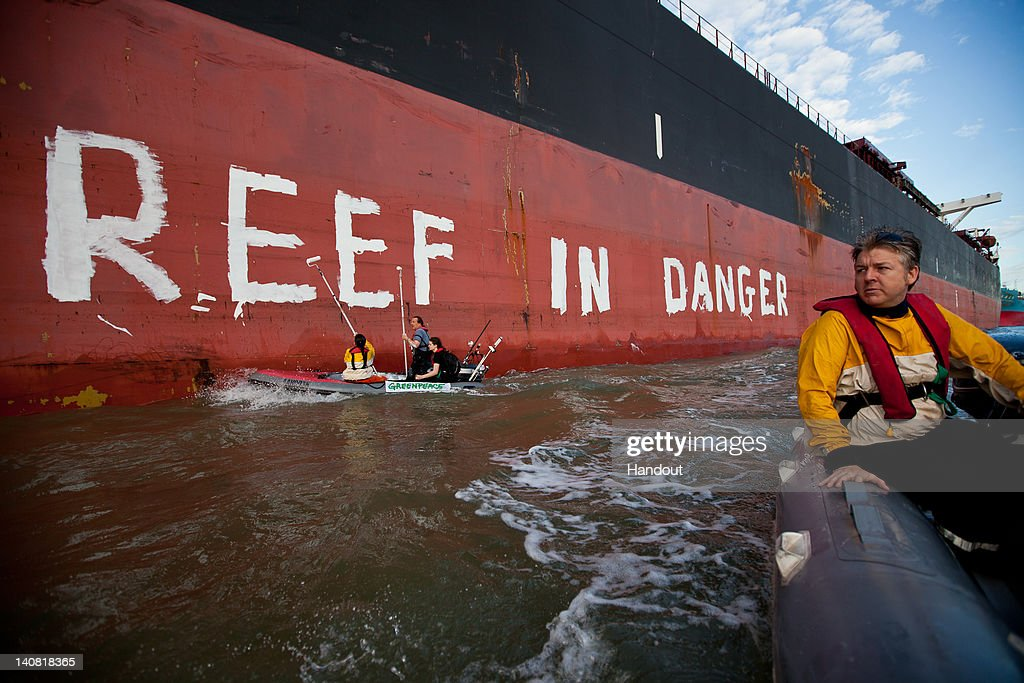 In this handout photo provided by Greenpeace, Activists paint the message 'Reef in Danger' on the side of coal ship Chou San on March 7, 2012 in Gladstone, Australia. A delegation from UNESCO is arriving in Gladstone today to assess threats to the Great Barrier Reef, both existing projects and the expected increase in transport through the World Heritage area following a planned coal mine expansion.