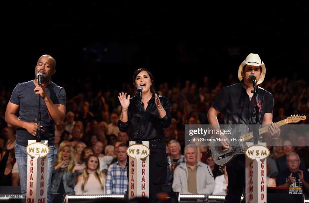 In this handout photo provided by Hand in Hand, Darius Rucker, Demi Lovato, and Brad Paisley perform onstage during Hand in Hand: A Benefit for Hurricane Relief at the Grand Ole Opry House on September 12, 2017 in Nashville, Tennessee.