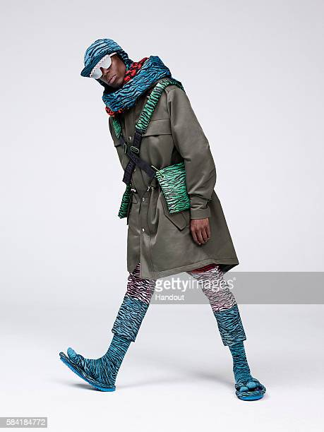 In this handout photo provided by HM Oko Ebombo performance artist and frontman of the band 19 wears KENZO x HM parka with removable printed collar...