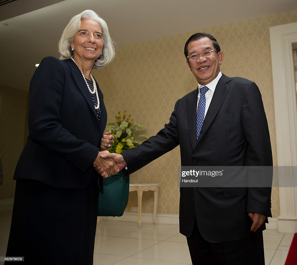 In this handout photo provided by IMF, International Monetary Fund Managing Director <a gi-track='captionPersonalityLinkClicked' href=/galleries/search?phrase=Christine+Lagarde&family=editorial&specificpeople=566337 ng-click='$event.stopPropagation()'>Christine Lagarde</a> (L) is greeted by Prime Minister <a gi-track='captionPersonalityLinkClicked' href=/galleries/search?phrase=Hun+Sen&family=editorial&specificpeople=224084 ng-click='$event.stopPropagation()'>Hun Sen</a> (R) at the Peace Palace December 2, 2013 in Phnom Penh, Cambodia. Lagarde is on a three country visit to Asia.