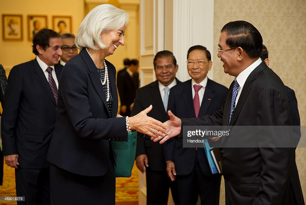 In this handout photo provided by IMF, International Monetary Fund Managing Director Christine Lagarde shakes hands with Prime Minister Hun Sen (R) at the Peace Palace December 2, 2013 in Phnom Penh, Cambodia. Lagarde is on a three country visit to Asia.