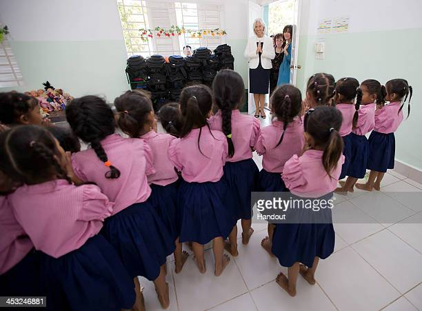 In this handout photo provided by IMF International Monetary Fund Managing Director Christine Lagarde greets school girls at Toutes a l'Ecole school...