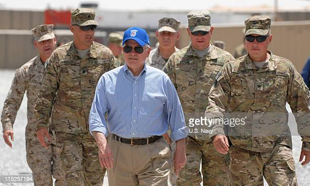 In this handout photo provided by ISAF Regional Command US Secretary of Defense Robert Gates walks with a group of service members at Forward...