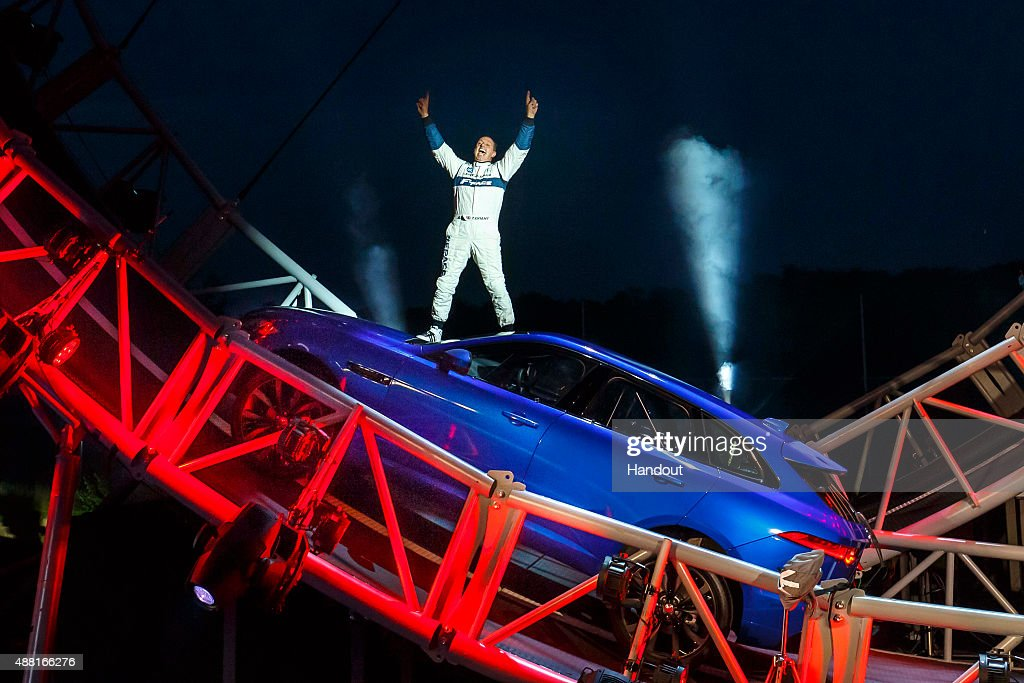 In this handout photo provided by Jaguar Terry Grant stands on the roof of his Jaguar FPace as celebrates breaking the Guinness World Record for...