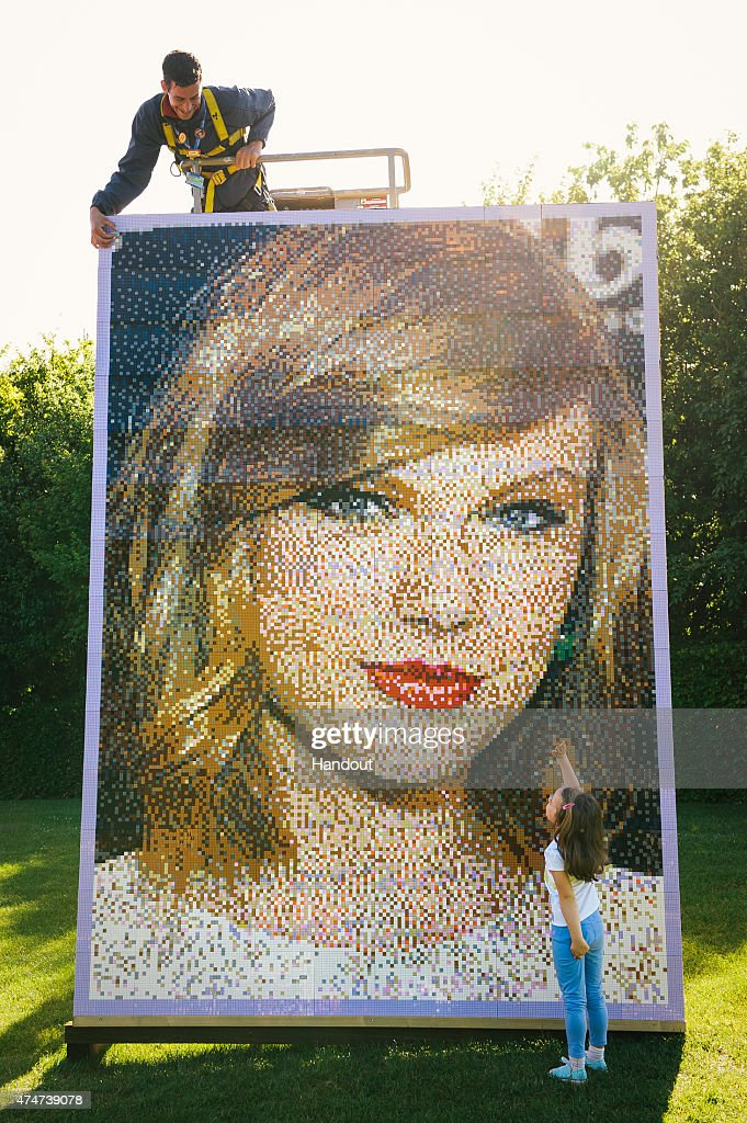 In this handout photo provided by Legoland, Kitty Baker, age 5, looks up at Legoland employee Pete Goodchild as he puts the finishing touches on the mosaic as the Giant Lego Mosaic of 'Celebrity Best Friend' Taylor Swift is revealed at The LEGOLAND Windsor Resort on May 25, 2015 in Windsor, England.
