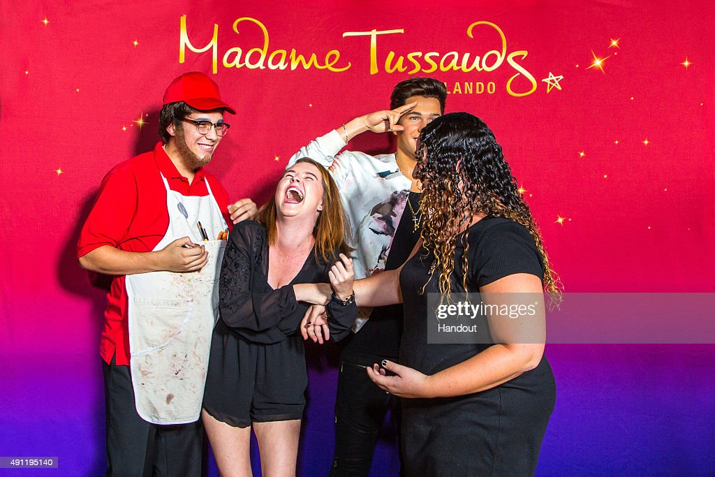 In this handout photo provided by Madame Tussauds Orlando singer Austin Mahone pranks fans by dressing up as a Madame Tussauds employee at Madame...