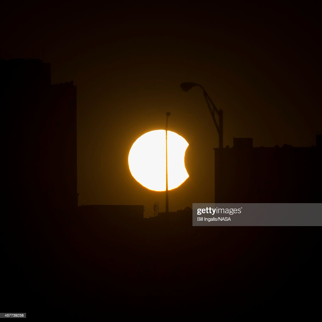 In this handout photo provided by NASA a partial solar eclipse is visible just before sunset October 23 in Arlington Virginia A partial eclipse...