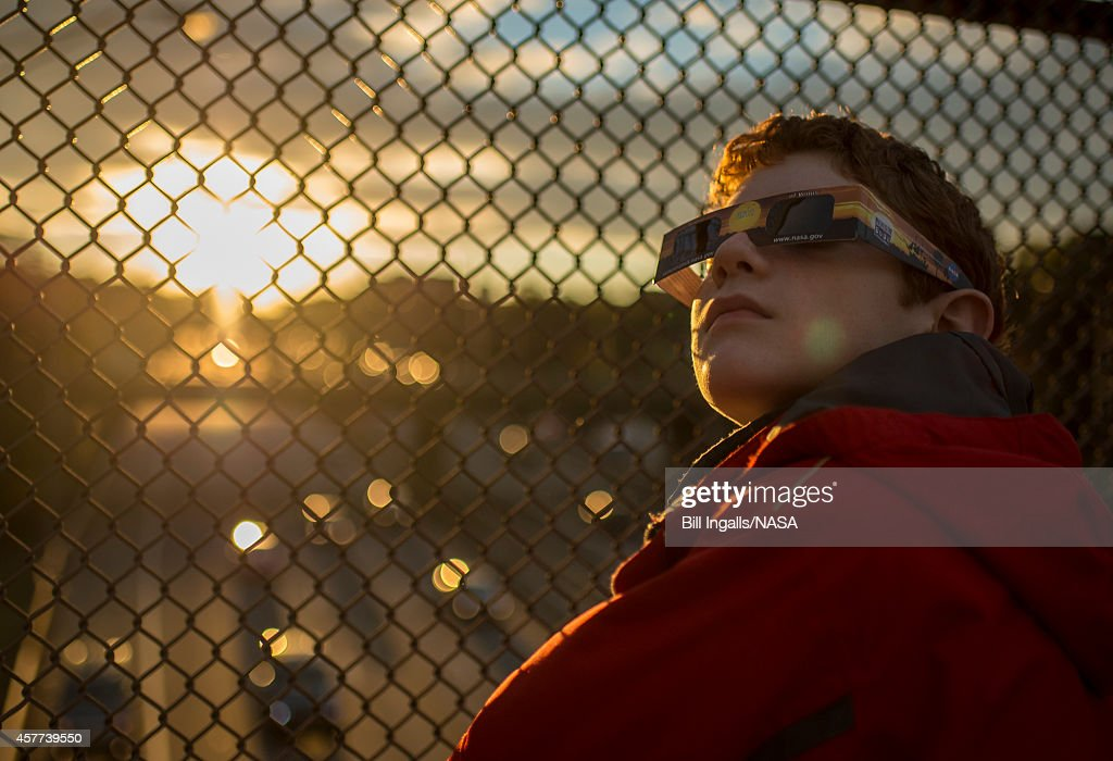 In this handout photo provided by NASA Alex Frye uses special viewing glasses to look at a partial solar eclipse from a highway overpass October 23...