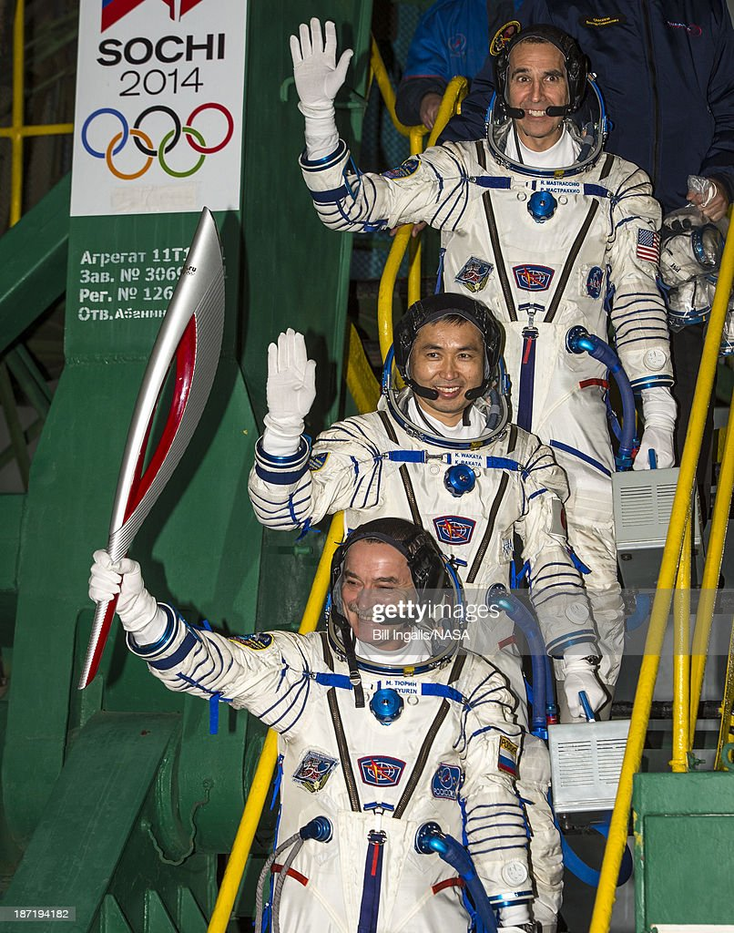 In this handout photo provided by NASA, Expedition 38 Soyuz Commander Mikhail Tyurin of Roscosmos, holding the Olympic torch, Flight Engineer <a gi-track='captionPersonalityLinkClicked' href=/galleries/search?phrase=Koichi+Wakata&family=editorial&specificpeople=220363 ng-click='$event.stopPropagation()'>Koichi Wakata</a> of the Japan Aerospace Exploration Agency, and, Flight Engineer Rick Mastracchio of NASA (top), wave farewell prior to boarding the Soyuz TMA-11M rocket for launch, on November 7, 2013 at the Baikonur Cosmodrome in Baikonur, Kazakhstan. The Olympic torch has a four-day visit to the International Space Station. Tyurin, Mastracchio, and, Wakata will spend the next six months aboard the International Space Station.