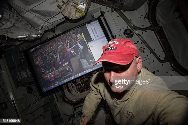 In this handout photo provided by NASA NASA astronaut Scott Kelly takes a break aboard the International Space Station to root for the Houston Texans...
