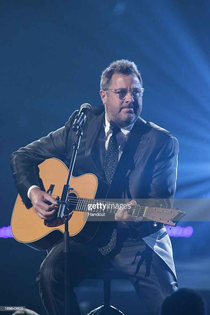 In this handout photo provided by NBC, <a gi-track='captionPersonalityLinkClicked' href=/galleries/search?phrase=Vince+Gill&family=editorial&specificpeople=215309 ng-click='$event.stopPropagation()'>Vince Gill</a> performs during the Healing in the Heartland: Relief Benefit Concert held at the Chesapeake Arena on May 29, 2013 in Oklahoma City, Oklahoma.