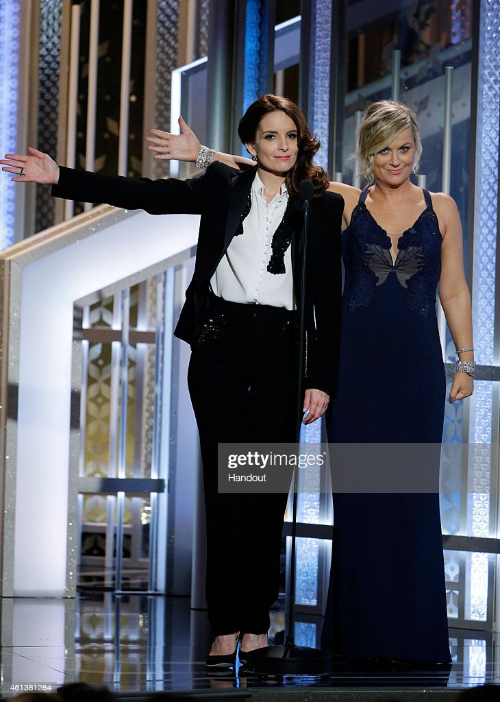 In this handout photo provided by NBCUniversal Hosts Tina Fey and Amy Poehler speak onstage during the 72nd Annual Golden Globe Awards at The Beverly...