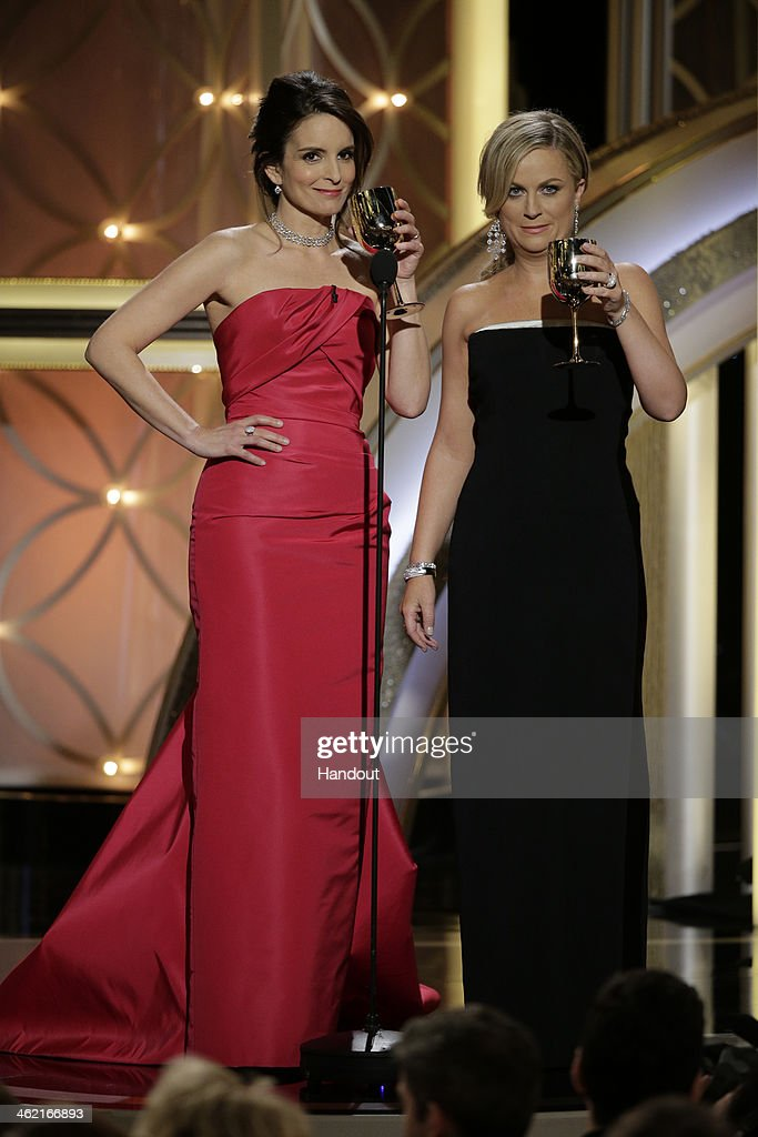 In this handout photo provided by NBCUniversal Hosts Tina Fey and Amy Poehler speak onstage during the 71st Annual Golden Globe Award at The Beverly...
