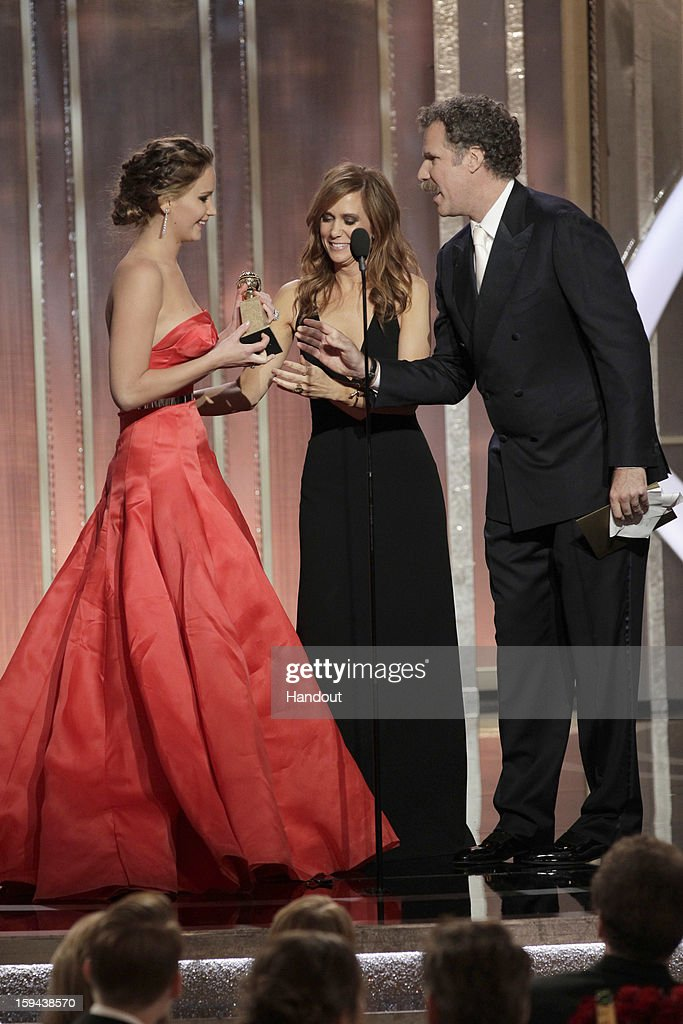 In this handout photo provided by NBCUniversal, Kristen Wiig and Will Ferrell present the Best Actress - Motion Picture, Comedy or Musical award to Jennifer Lawrence on stage during the 70th Annual Golden Globe Awards at the Beverly Hilton Hotel International Ballroom on January 13, 2013 in Beverly Hills, California.
