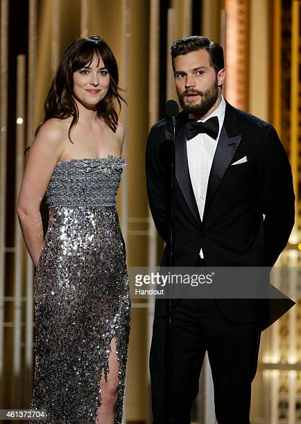 In this handout photo provided by NBCUniversal Presenters Dakota Johnson and Jamie Dornan speak onstage during the 72nd Annual Golden Globe Awards at...