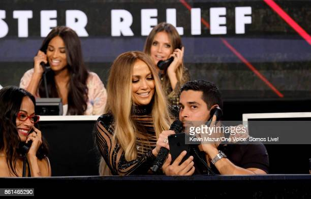 In this handout photo provided by One Voice Somos Live actor Zoe Saldana singer Jennifer Lopez and actor Wilmer Valderrama speak onstage during 'One...