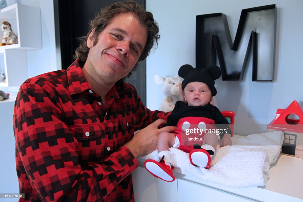 In this handout photo provided by Perez Hilton Perez Hilton poses with his one month old son Mario Lavandeira III during a portrait on March 17 2013...