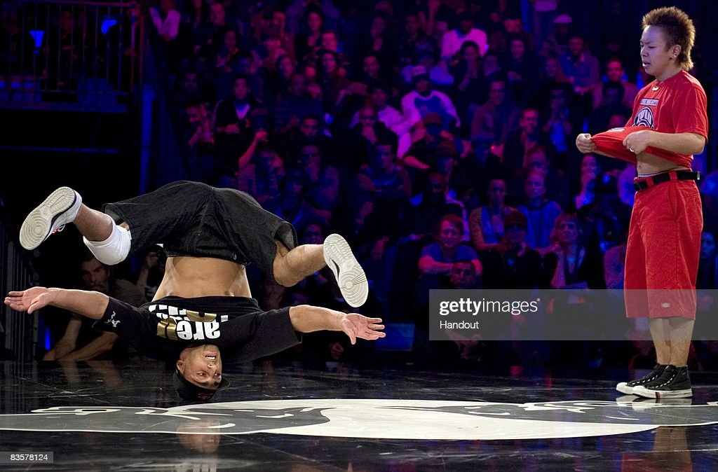In this handout photo provided by Red Bull, Lil Ceng of Germany performs as Taisuke of Japan watches on during the Red Bull BC One breakdance competition on November 5, 2008 in Paris, France. Sixteen of the world's best B-Boys compete in one-on-one knockout battles to determine the winner.