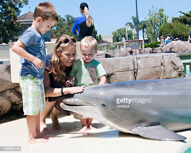 In this handout photo provided by SeaWorld San Diego singer/songwriter Sheryl Crow and her sons Wyatt Crow and Levi Crow make a new friend in Steime...