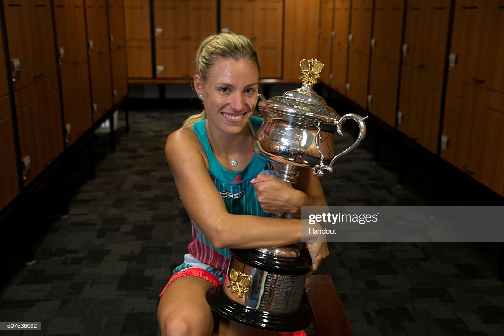 In this handout photo provided by Tennis Australia, Angelique Kerber of Germany poses with the Daphne Akhurst Trophy in the players change rooms after winning her Women's Singles Final match against Serena Williams of the United States during day 13 of the 2016 Australian Open at Melbourne Park on January 30, 2016 in Melbourne, Australia.