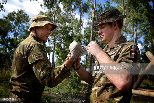 In this handout photo provided by the Australian Defence Force Prince Harry applies a bandage to Lieutenant Gerard Hinchliffe during Exercise Thunder...