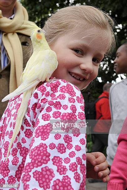 In this handout photo provided by the Belgian Royal Palace Princess Elizabeth of Belgium holds a parrot as she attends a Summer Photocall at...