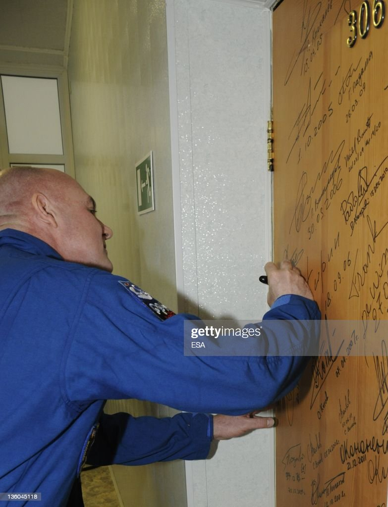 In this handout photo provided by the European Space Agency (ESA), ESA astronaut André Kuipers signs the door of suite 306 in the Cosmonaut Hotel on December 21, 2011 at Baikonur Cosmodrome in Kazakhstan. The Soyuz TMA-03M spacecraft is due to launch today from Baikonur Cosmodrome, ahead of a five month expedition to the International Space Station.