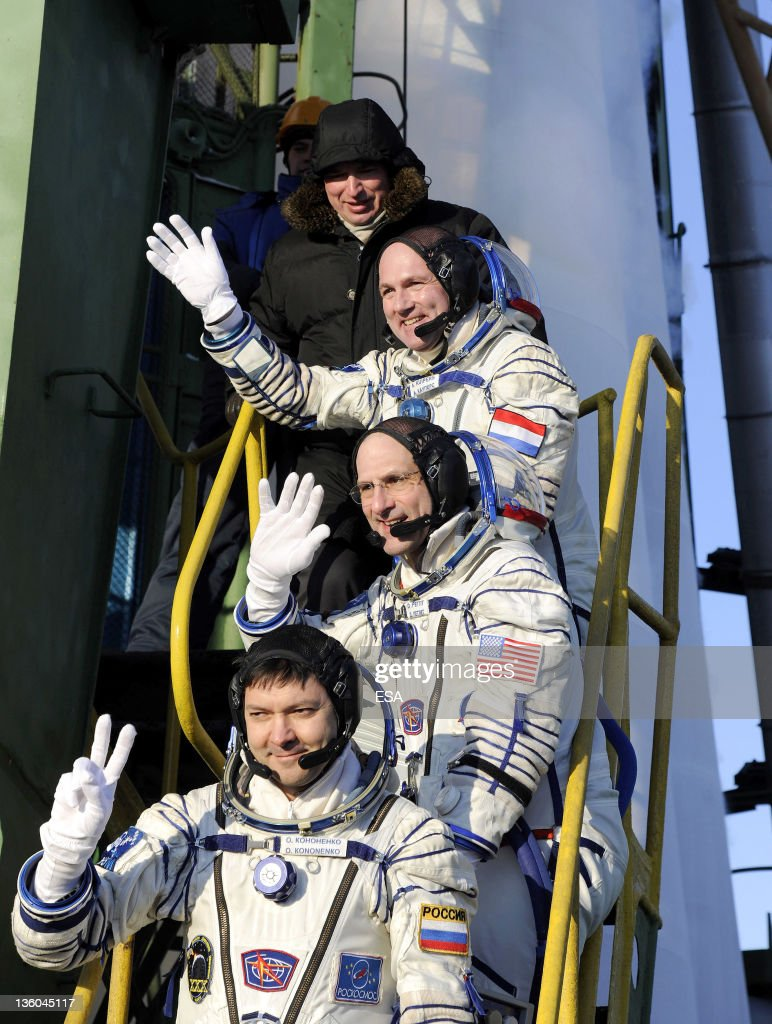 In this handout photo provided by the European Space Agency (ESA), ESA Russian cosmonaut Oleg Kononenko, NASA astronaut Don Pettit and ESA astronaut André Kuipers wave goodbye to the crowd gathered at the foot of the Soyuz launch pad stairs before taking the elevator to the top of the Soyuz rocket on December 21, 2011 at Baikonur Cosmodrome in Kazakhstan. The Soyuz TMA-03M spacecraft is due to launch today from Baikonur Cosmodrome, ahead of a five month expedition to the International Space Station.