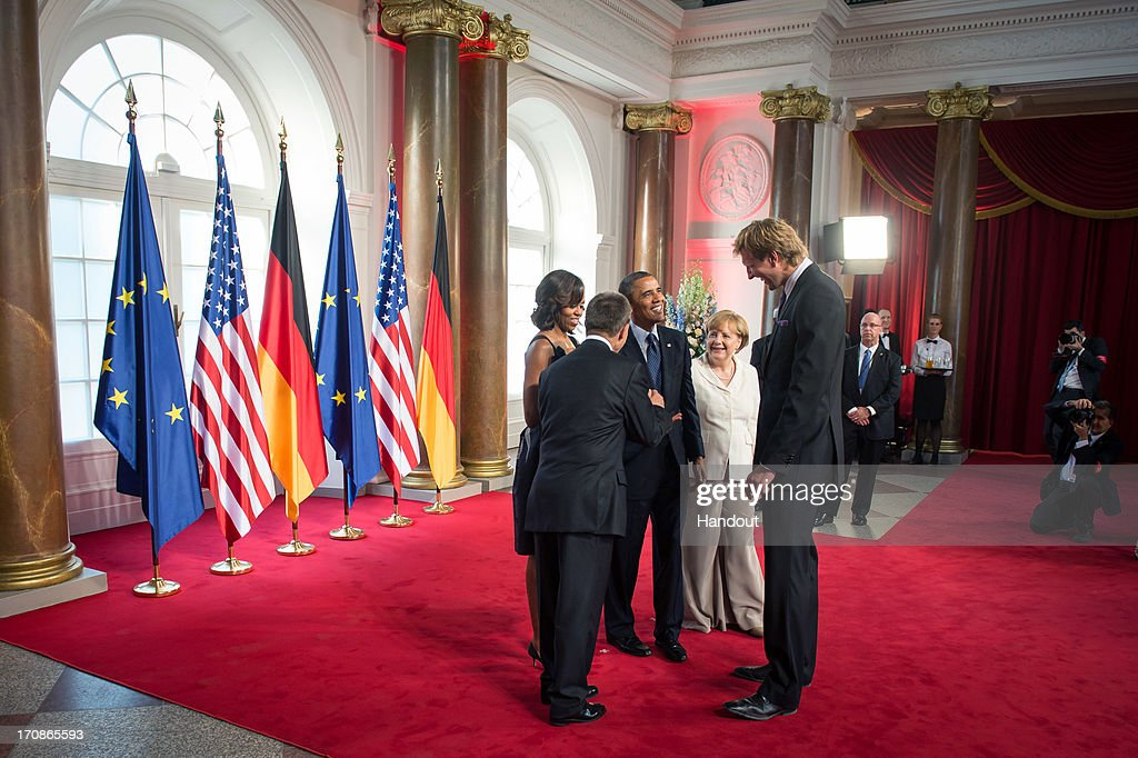 In this handout photo provided by the German Government Press Office (BPA), U.S. President <a gi-track='captionPersonalityLinkClicked' href=/galleries/search?phrase=Barack+Obama&family=editorial&specificpeople=203260 ng-click='$event.stopPropagation()'>Barack Obama</a> and First Lady <a gi-track='captionPersonalityLinkClicked' href=/galleries/search?phrase=Michelle+Obama&family=editorial&specificpeople=2528864 ng-click='$event.stopPropagation()'>Michelle Obama</a> stand alongside German Chancellor <a gi-track='captionPersonalityLinkClicked' href=/galleries/search?phrase=Angela+Merkel&family=editorial&specificpeople=202161 ng-click='$event.stopPropagation()'>Angela Merkel</a> as they meet NBA basketball player <a gi-track='captionPersonalityLinkClicked' href=/galleries/search?phrase=Dirk+Nowitzki&family=editorial&specificpeople=201490 ng-click='$event.stopPropagation()'>Dirk Nowitzki</a> (R) and president of the Federation of German Industries (BDI) Ulrich Grillo (2nd L) at the beginning of a dinner in honor of President Obama in the Orangery of Charlottenburg Palace on June 19, 2013 in Berlin, Germany. Obama is visiting Berlin for the first time during his presidency with a speech at the Brandenburg Gate to be the highlight. Obama will be speaking close to the 50th anniversary of the historic speech by then U.S. President John F. Kennedy in Berlin in 1963, during which he proclaimed the famous sentence 'Ich bin ein Berliner'.