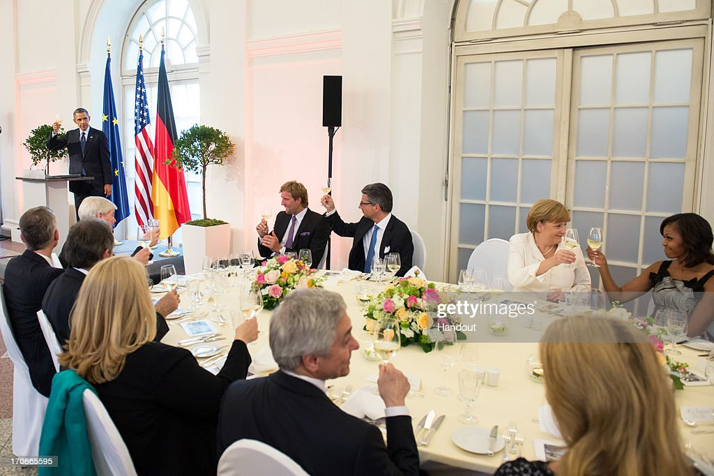 In this handout photo provided by the German Government Press Office (BPA), U.S. President <a gi-track='captionPersonalityLinkClicked' href=/galleries/search?phrase=Barack+Obama&family=editorial&specificpeople=203260 ng-click='$event.stopPropagation()'>Barack Obama</a> raises a toast as NBA basketball player <a gi-track='captionPersonalityLinkClicked' href=/galleries/search?phrase=Dirk+Nowitzki&family=editorial&specificpeople=201490 ng-click='$event.stopPropagation()'>Dirk Nowitzki</a>, president of the Federation of German Industries (BDI) Ulrich Grillo, German Chancellor <a gi-track='captionPersonalityLinkClicked' href=/galleries/search?phrase=Angela+Merkel&family=editorial&specificpeople=202161 ng-click='$event.stopPropagation()'>Angela Merkel</a> and First Lady <a gi-track='captionPersonalityLinkClicked' href=/galleries/search?phrase=Michelle+Obama&family=editorial&specificpeople=2528864 ng-click='$event.stopPropagation()'>Michelle Obama</a> look on during a dinner in honor of President Obama in the Orangery of Charlottenburg Palace on June 19, 2013 in Berlin, Germany. Obama is visiting Berlin for the first time during his presidency with a speech at the Brandenburg Gate to be the highlight. Obama will be speaking close to the 50th anniversary of the historic speech by then U.S. President John F. Kennedy in Berlin in 1963, during which he proclaimed the famous sentence 'Ich bin ein Berliner'.
