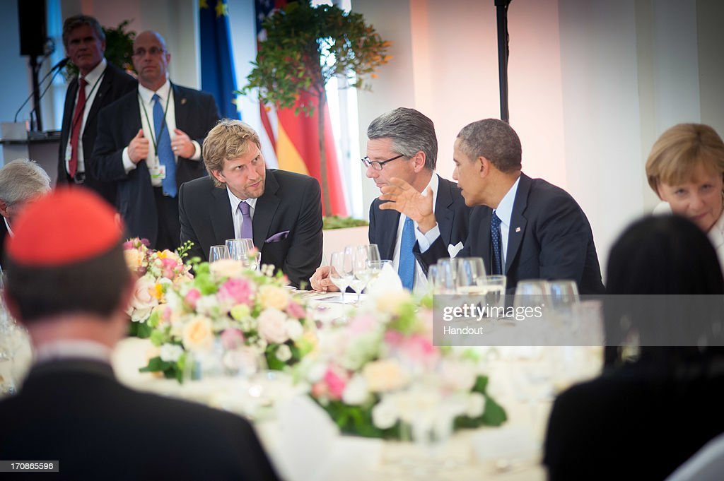 In this handout photo provided by the German Government Press Office (BPA), U.S. President <a gi-track='captionPersonalityLinkClicked' href=/galleries/search?phrase=Barack+Obama&family=editorial&specificpeople=203260 ng-click='$event.stopPropagation()'>Barack Obama</a> talks with NBA basketball player <a gi-track='captionPersonalityLinkClicked' href=/galleries/search?phrase=Dirk+Nowitzki&family=editorial&specificpeople=201490 ng-click='$event.stopPropagation()'>Dirk Nowitzki</a> (R) and president of the Federation of German Industries (BDI) Ulrich Grillo (C) as he sits alongside sits alongside German Chancellor Angela Merkel at the beginning of a dinner in honor of President Obama in the Orangery of Charlottenburg Palace on June 19, 2013 in Berlin, Germany. Obama is visiting Berlin for the first time during his presidency with a speech at the Brandenburg Gate to be the highlight. Obama will be speaking close to the 50th anniversary of the historic speech by then U.S. President John F. Kennedy in Berlin in 1963, during which he proclaimed the famous sentence 'Ich bin ein Berliner'.