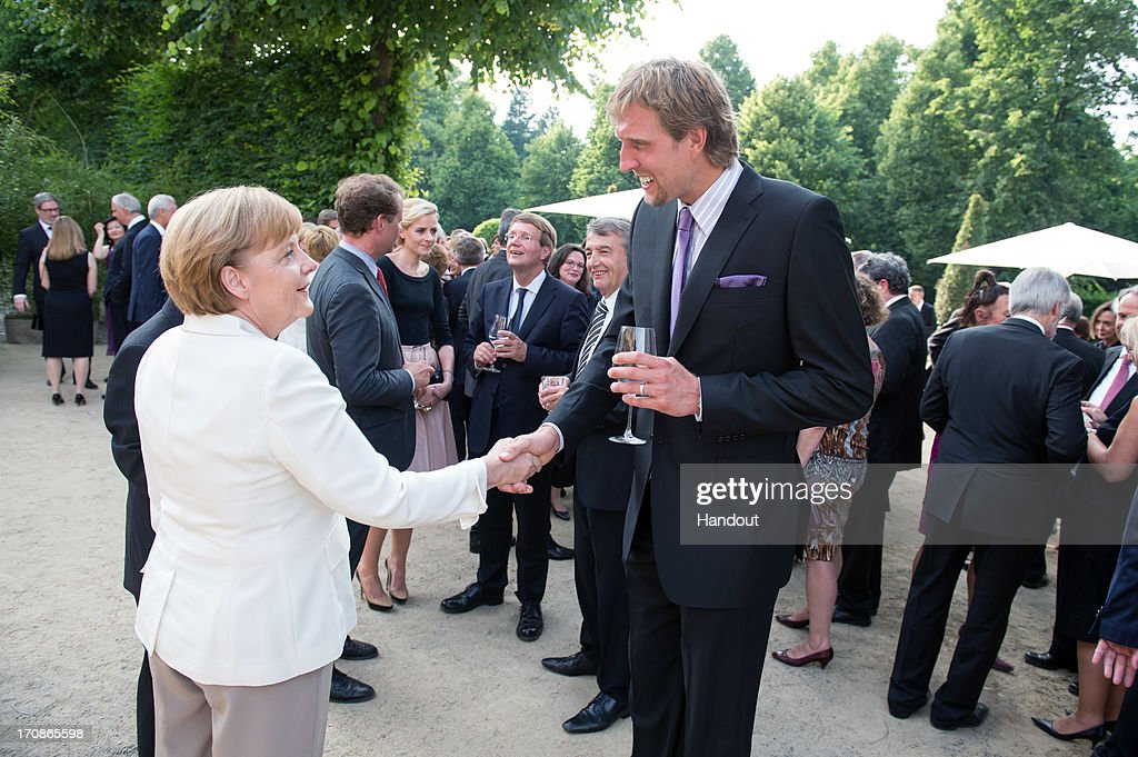 In this handout photo provided by the German Government Press Office (BPA), German Chancellor <a gi-track='captionPersonalityLinkClicked' href=/galleries/search?phrase=Angela+Merkel&family=editorial&specificpeople=202161 ng-click='$event.stopPropagation()'>Angela Merkel</a> shakes hands with NBA basketball player <a gi-track='captionPersonalityLinkClicked' href=/galleries/search?phrase=Dirk+Nowitzki&family=editorial&specificpeople=201490 ng-click='$event.stopPropagation()'>Dirk Nowitzki</a> (R) during a dinner held in honor of U.S. President Barack Obama in the Orangery of Charlottenburg Palace on June 19, 2013 in Berlin, Germany. Obama is visiting Berlin for the first time during his presidency with a speech at the Brandenburg Gate to be the highlight. Obama will be speaking close to the 50th anniversary of the historic speech by then U.S. President John F. Kennedy in Berlin in 1963, during which he proclaimed the famous sentence 'Ich bin ein Berliner'.