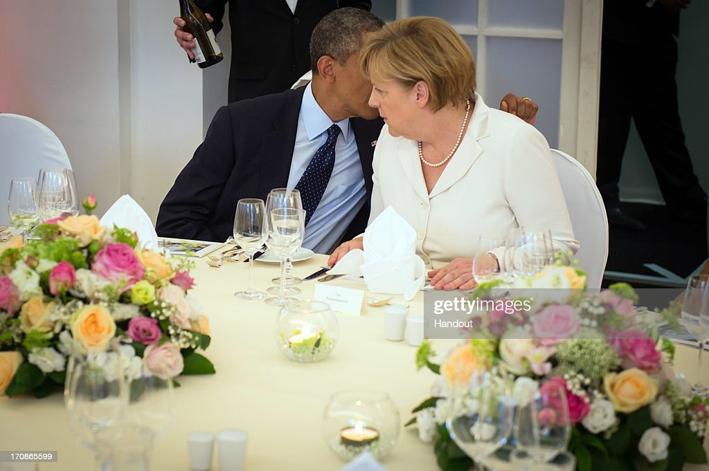 In this handout photo provided by the German Government Press Office (BPA), U.S. President <a gi-track='captionPersonalityLinkClicked' href=/galleries/search?phrase=Barack+Obama&family=editorial&specificpeople=203260 ng-click='$event.stopPropagation()'>Barack Obama</a> talks with German Chancellor <a gi-track='captionPersonalityLinkClicked' href=/galleries/search?phrase=Angela+Merkel&family=editorial&specificpeople=202161 ng-click='$event.stopPropagation()'>Angela Merkel</a> (R) at the beginning of a dinner held in honor of President Obama in the Orangery of Charlottenburg Palace on June 19, 2013 in Berlin, Germany. Obama is visiting Berlin for the first time during his presidency with a speech at the Brandenburg Gate to be the highlight. Obama will be speaking close to the 50th anniversary of the historic speech by then U.S. President John F. Kennedy in Berlin in 1963, during which he proclaimed the famous sentence 'Ich bin ein Berliner'.