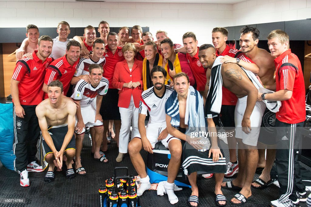 In this handout photo provided by the German Government Press Office (BPA), German Chancellor Angela Merkel visits the German National team in their dressing room after the 2014 FIFA World Cup Brazil Group G match between Germany and Portugal at Arena Fonte Nova on June 16, 2014 in Salvador, Brazil.