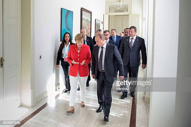 In this handout photo provided by the German Government Press Office German Chancellor Angela Merkel meets Russian President Vladimir Putin at...