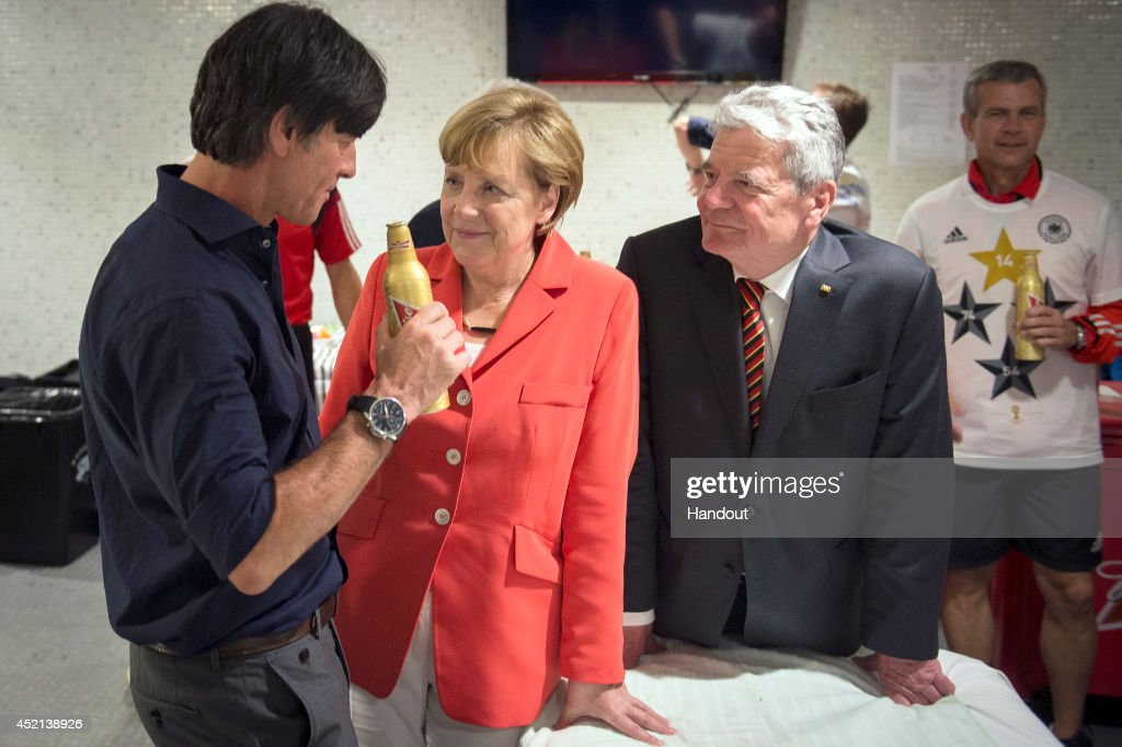In this handout photo provided by the German Government Press Office (BPA), German Chancellor Angela Merkel (C) and German President Joachim Gauck (R) talk to head coach Joachim Loew of Germany after winning the 2014 FIFA World Cup Brazil Final match against Argentina at Maracana on July 13, 2014 in Rio de Janeiro, Brazil.