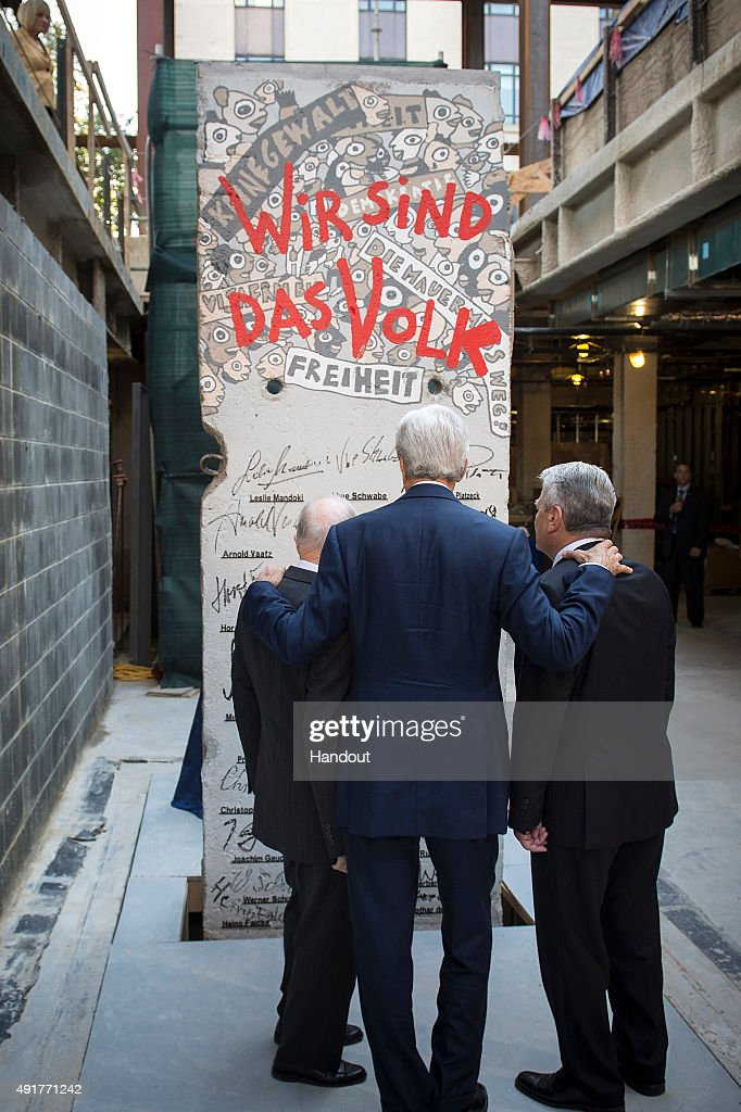 In this handout photo provided by the German Government Press Office (BPA) The former adviser to the US President Bush, Brent Scowcroft, (L) German President Joachim Gauck (R) and U.S. Secretary of State John Kerry look at a piece of the Berlin Wall, (with the signatures of Bush, Gorbachev, Merkel and Genscher) for the new Center Diplomacy Ministry of Foreign Affairs on October 8, 2016 in Washington DC.