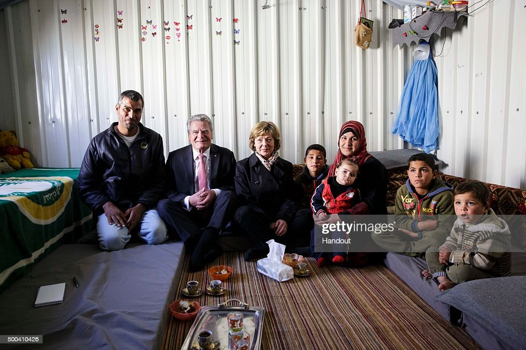 In this handout photo provided by the German Government Press Office (BPA) German President Joachim Gauck (2L) and his partner, Daniela Schadt speak with a Syrian family at their accomodation on March 16, 2015 in in Azraq, Jordan.