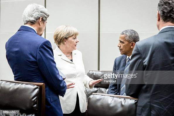 In this handout photo provided by the German Government Press Office German chancellor Angela Merkel speaks with US President Barack Obama and US...
