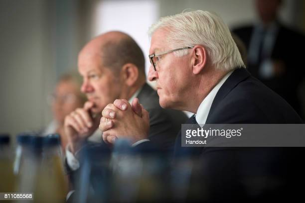 In this handout photo provided by the German Government Press Office German President FrankWalter Steinmeier and Mayor of Hamburg Olaf Scholz talk to...