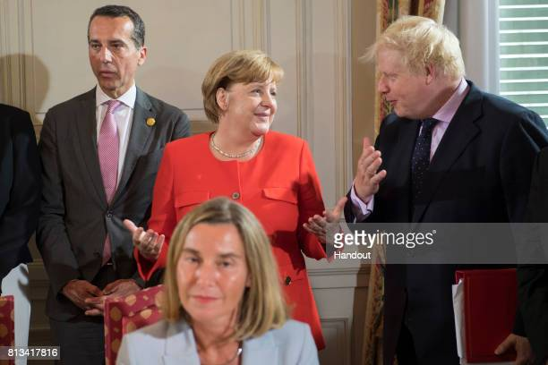 In this handout photo provided by the German Government Press Office German Chancellor Angela Merkel and the British Foreign Minister Boris Johnson...