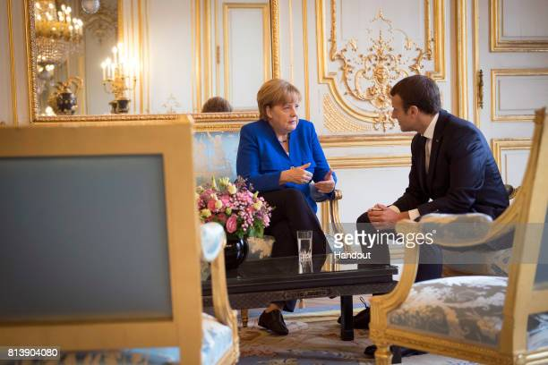 In this handout photo provided by the German Government Press Office German Chancellor Angela Merkel and the French President Emmanuel Macron speak...