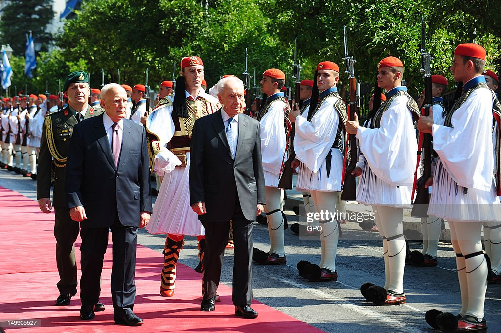 In this handout photo provided by the GPO, Israeli President Shimon Peres reviews an hounour guard with Greek President Karolos Papoulias on August 6, 2012 in Athens, Greece. Peres is on a three-day state visit to Greece.
