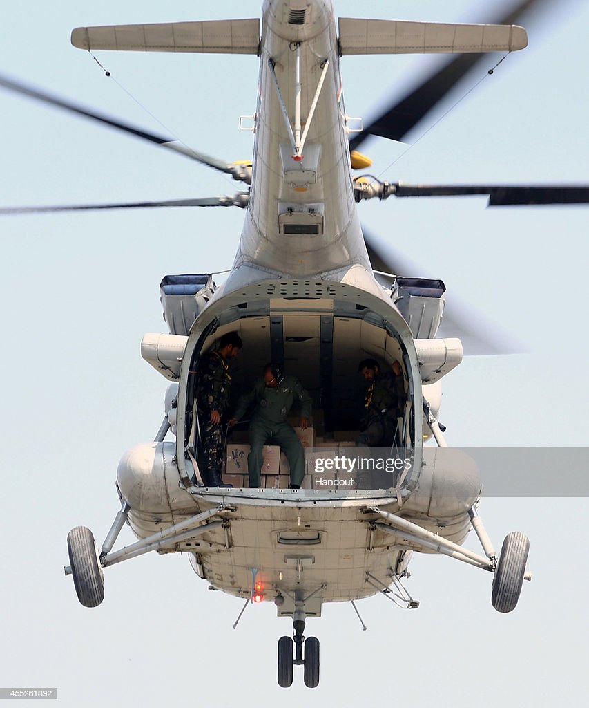 In this handout photo provided by the Indian Defence Ministry Members of Indian Air Force hover over a residential area before dropping aid in to the...