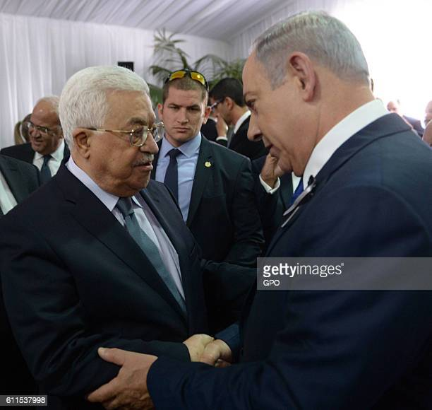 In this handout photo provided by the Israel Government Press Office Israeli Prime Minister Benjamin Netanyahu shakes hands with Palestinian...